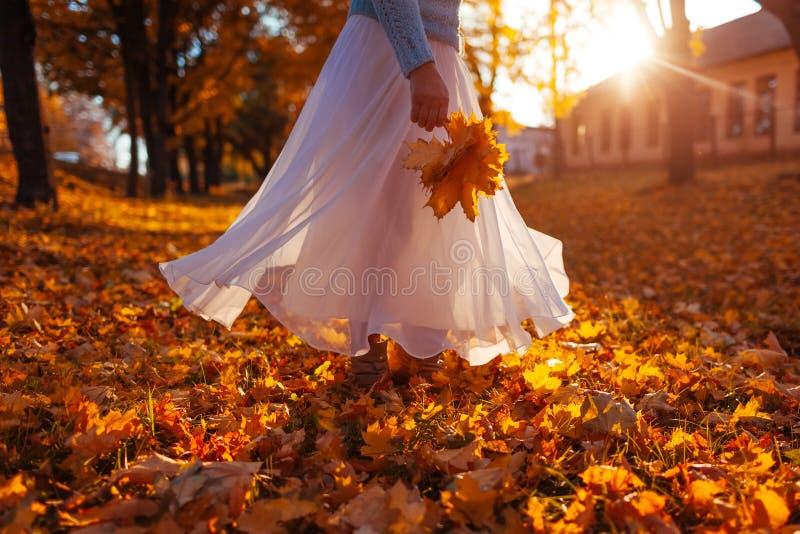 Baile de la mujer en el bosque del otoño que sostiene el ramo de hojas amarillas Señora que lleva la falda blanca elegante imagenes de archivo