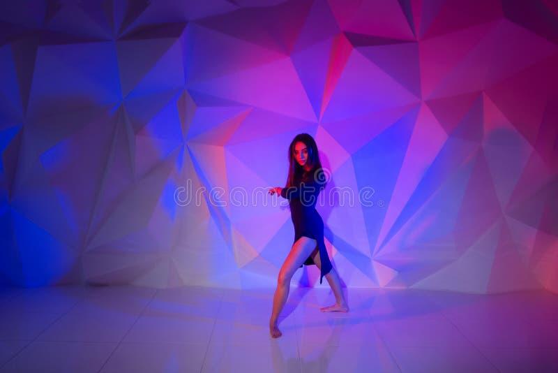 Baile de la mujer en el fondo de una pared multicolora hermosa Muchacha sola delgada atractiva con el pelo negro largo en a imagen de archivo