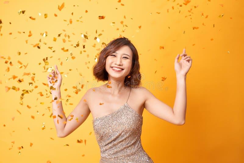 Baile de la mujer joven debajo del confeti en casa, celebrando cumplea?os fotos de archivo