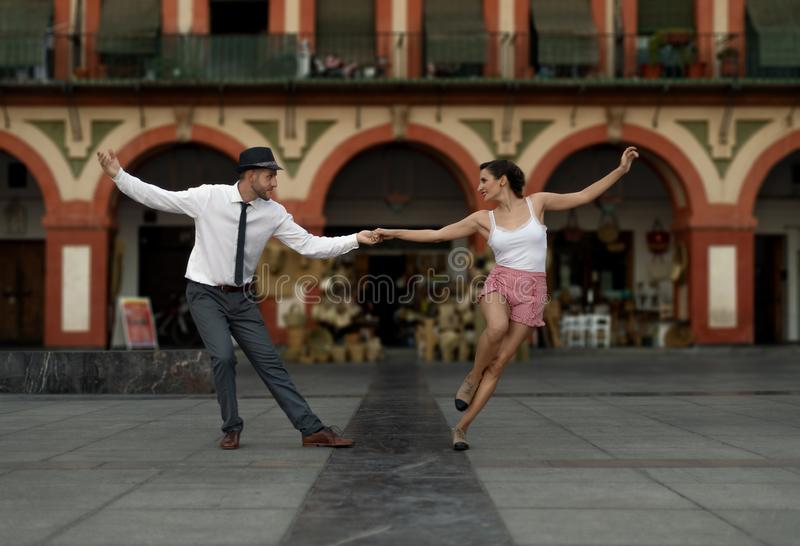 Baile de los bailarines del oscilación en un cuadrado de ciudad fotos de archivo