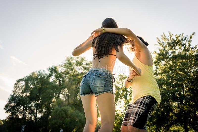 Baile de torneado de la mujer de Mann en la hierba en parque del verano imagen de archivo
