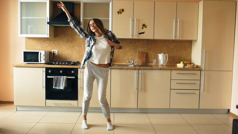 Baile divertido joven alegre de la mujer y canto con la cucharón mientras que teniendo tiempo libre en la cocina en casa fotografía de archivo libre de regalías