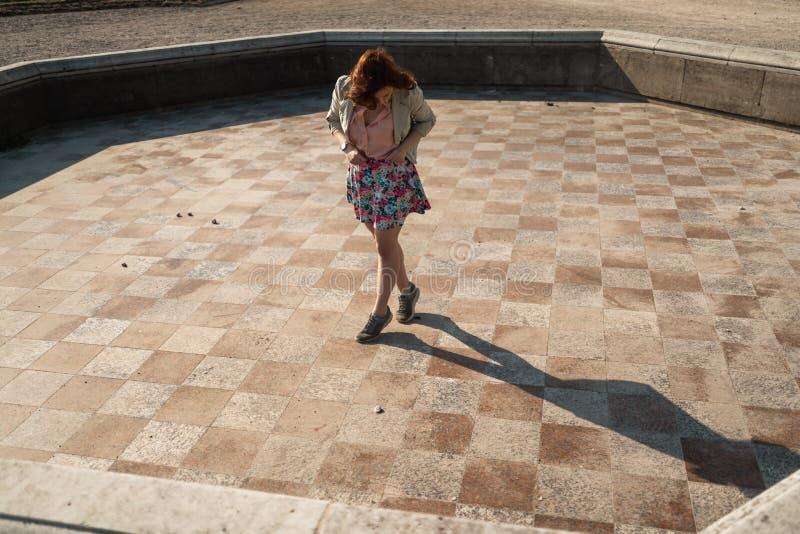 Baile feliz de la mujer joven en una fuente vacía que lleva una falda colorida fotografía de archivo libre de regalías