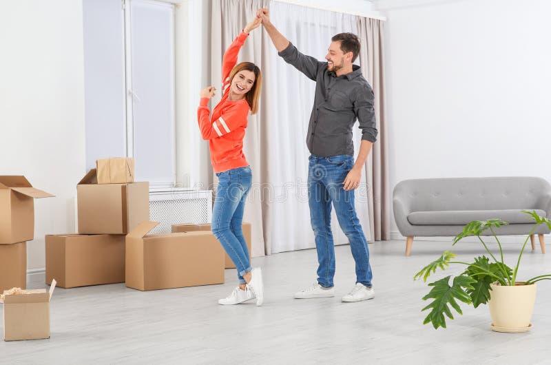 Baile feliz de los pares cerca de las cajas móviles en nueva casa fotografía de archivo
