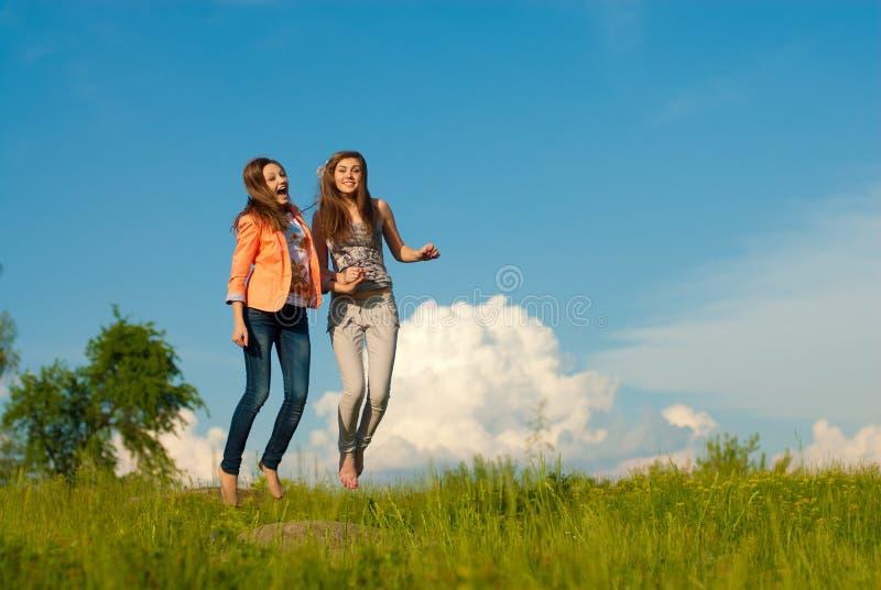 Baile feliz hermoso de dos mujeres jovenes y cielo azul fotografía de archivo