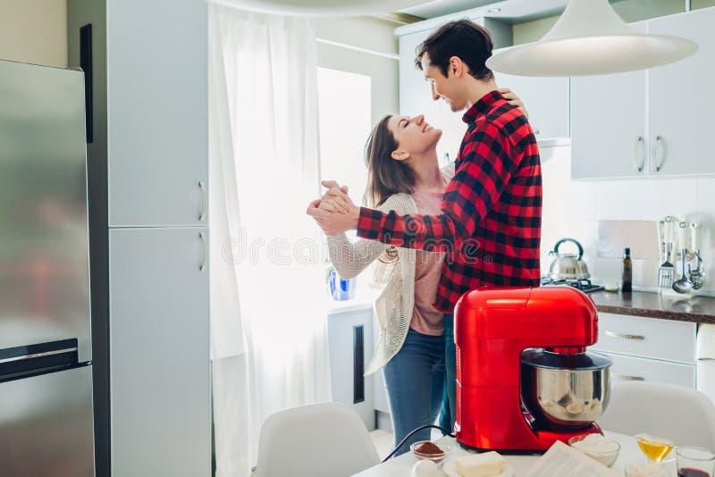 Baile feliz joven de los pares en cocina mientras que cocina con el procesador de alimentos Mujer y hombre que se relajan en casa fotos de archivo
