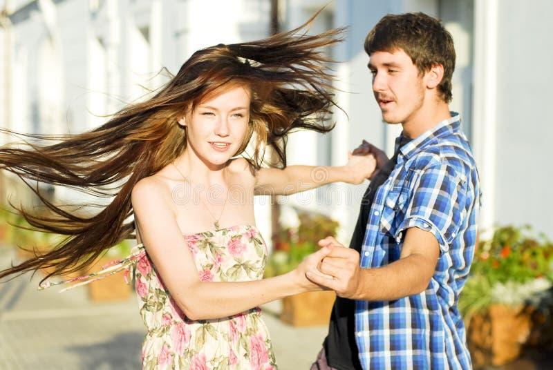 Baile feliz joven de los pares en la calle foto de archivo