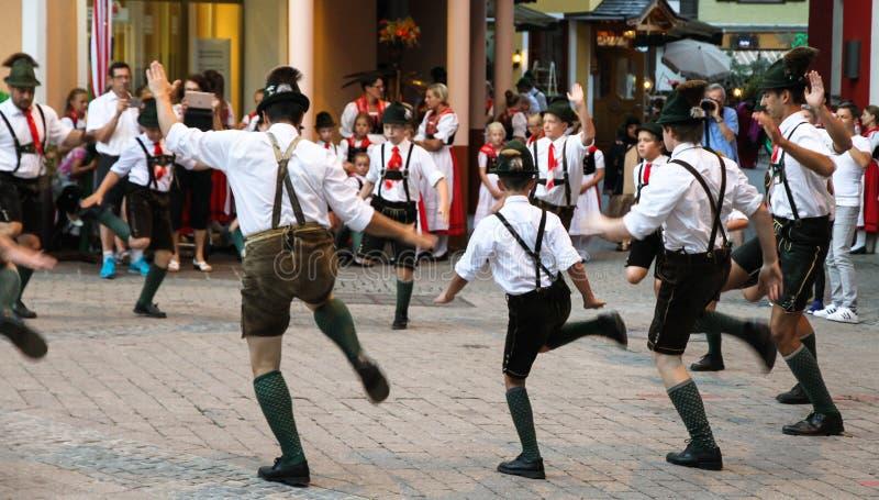 Baile folclórico austríaco tradicional que se realiza en las calles con los lederhosen y los dirndls tradicionales de la ropa de  imagenes de archivo