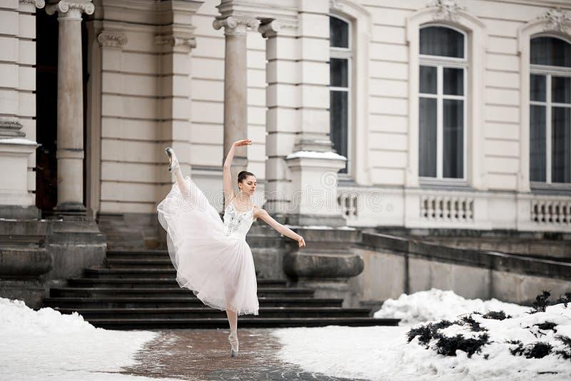 Baile hermoso de la bailarina al lado del edificio en fondo de la nieve fotos de archivo