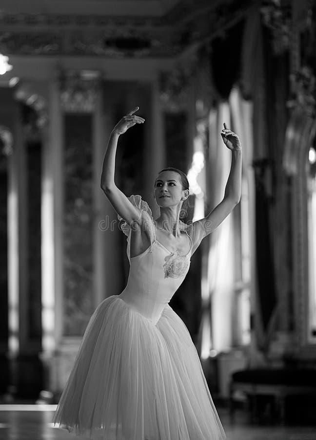 Baile hermoso de la bailarina en un pasillo lujoso contra la ventana fotos de archivo