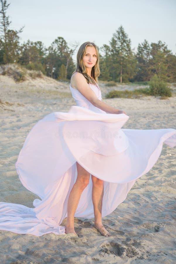 Baile hermoso de la muchacha en la playa imagen de archivo libre de regalías