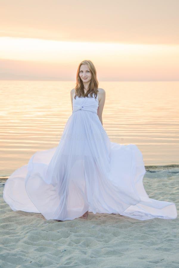 Baile hermoso de la muchacha en la playa foto de archivo