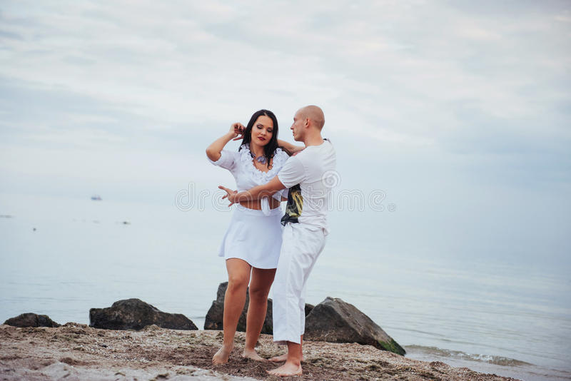 Baile inflamatorio hermoso de los pares en la playa foto de archivo libre de regalías