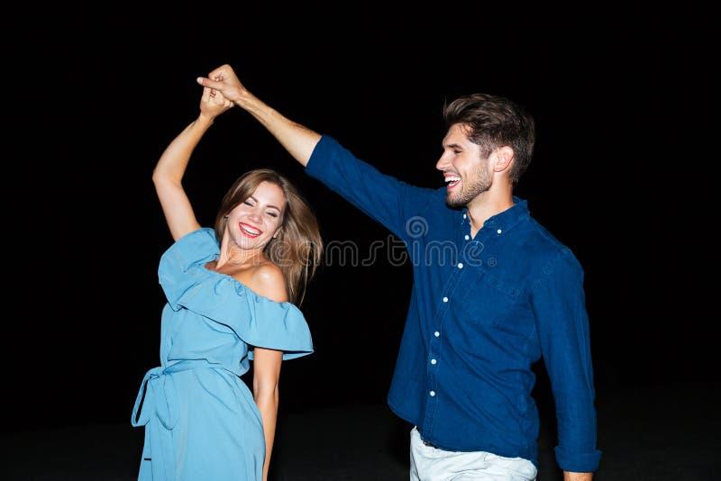 Baile joven alegre de los pares en la playa en la noche fotos de archivo