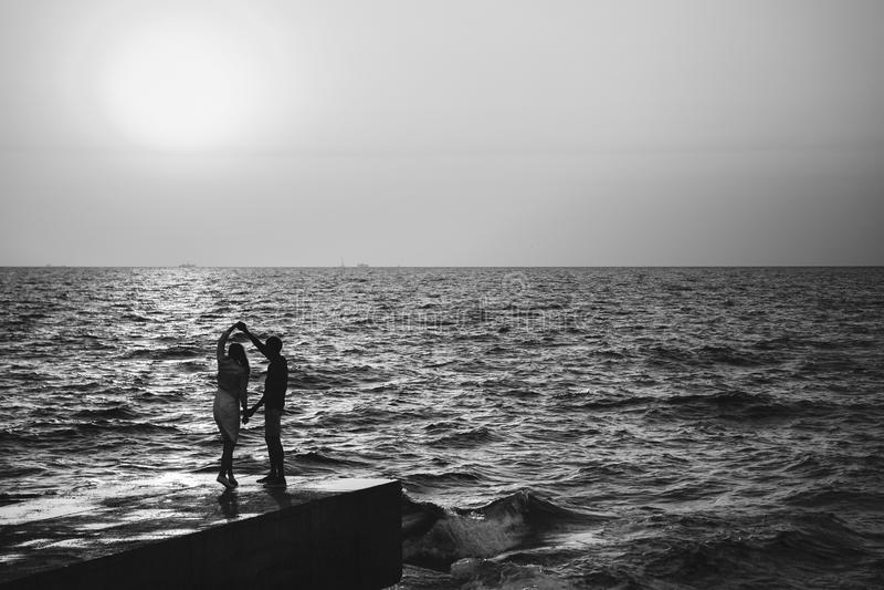 Baile joven de los pares en el embarcadero en el tiempo de verano de la playa fotografía de archivo