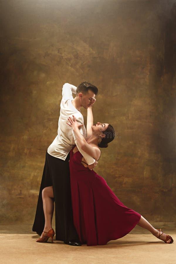 Baile los pares del salón de baile en el baile rojo del vestido en fondo del estudio foto de archivo