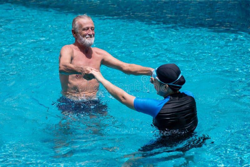 Baile mayor feliz de los pares en piscina junto Padre y ni?o que juegan junto Profesor que nada Llevar a cabo las manos, entrenam foto de archivo