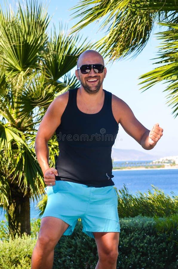 Baile muscular hermoso del hombre en jardín tropical foto de archivo libre de regalías
