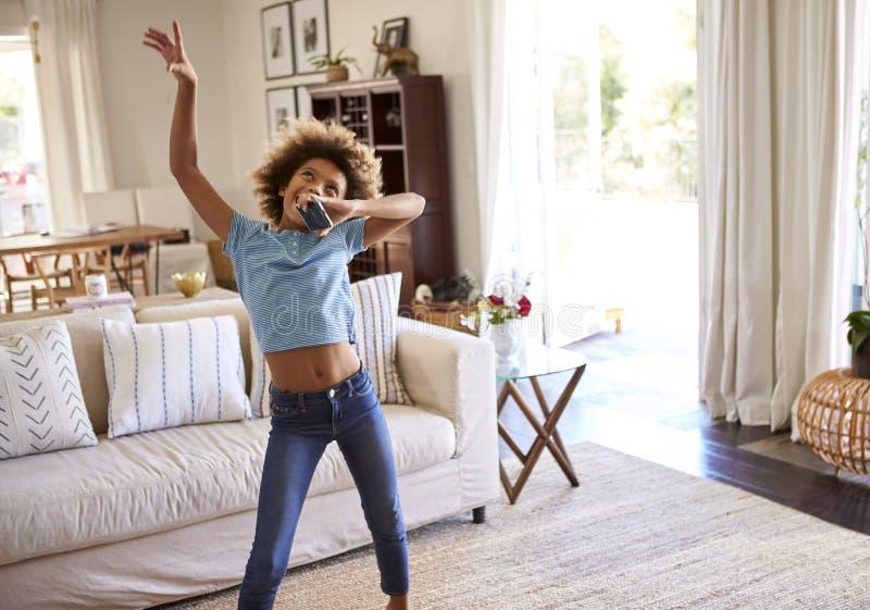 baile Pre-adolescente de la muchacha y canto adelante a la música en la sala de estar en casa usando su teléfono como micrófono,  imagen de archivo libre de regalías