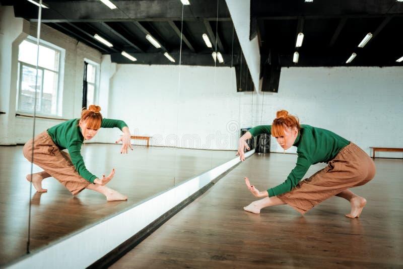 Baile profesional pelirrojo bonito del bailarín cerca del espejo fotografía de archivo