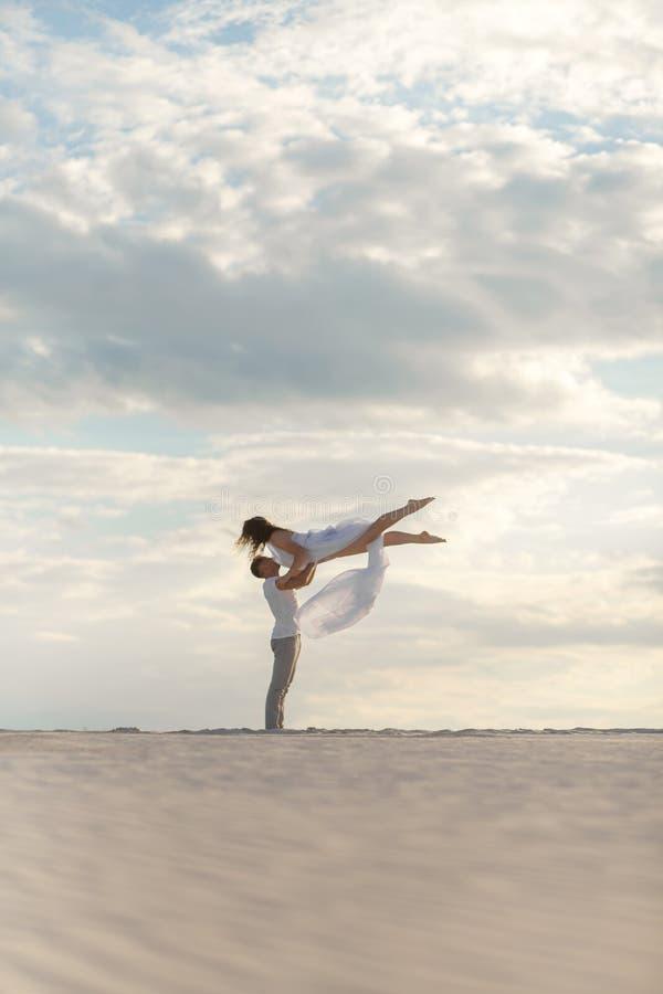 Baile romántico de los pares en desierto de la arena El individuo levanta a la muchacha sobre sí mismo Cielo de la puesta del sol foto de archivo