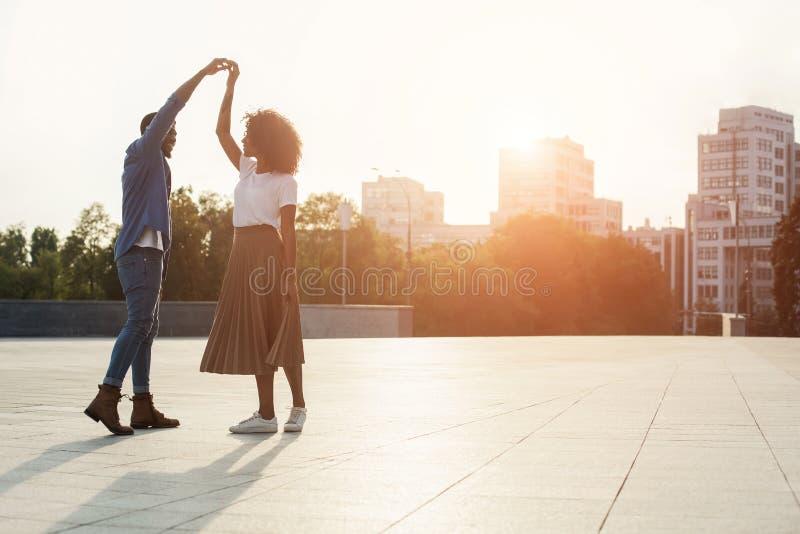 Baile rom?ntico de los pares en la puesta del sol y la diversi?n el tener, espacio de la copia foto de archivo