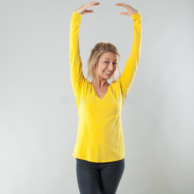 Baile rubio sonriente de la mujer 20s con las manos agraciadas para arriba foto de archivo