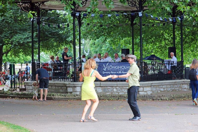 Baile a un concierto de la banda del aire abierto en un parque BRITÁNICO imagen de archivo libre de regalías