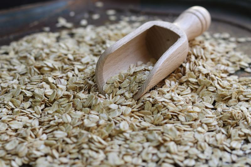 Bailer with oats flakes. Bailer of wood with oat flakes stock image