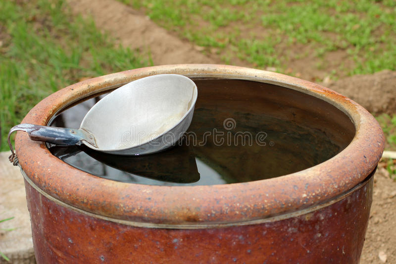 The bailer and the water tank. The tank is being filled with water stock photography