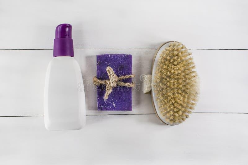 Bain étendu plat de station thermale sur le fond en bois blanc, produits de vue supérieure pour l'hygiène Brosse, savon et tube photo stock