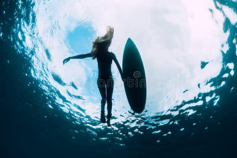 Bain de femme de surfer avec la planche de surf Fille de ressac dans l'oc?an photographie stock libre de droits