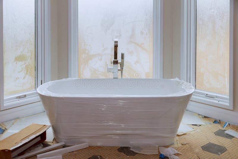 Bain principal dans la maison de nouvelle construction avec le baquet blanc image stock