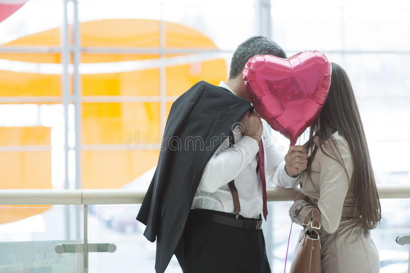 Baiser d'homme et de femme derrière le ballon en forme de coeur photographie stock