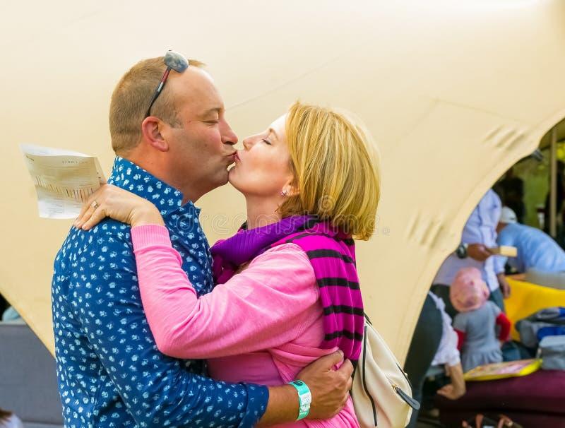 Baiser de couples âgé par milieu à l'événement de vin photos libres de droits
