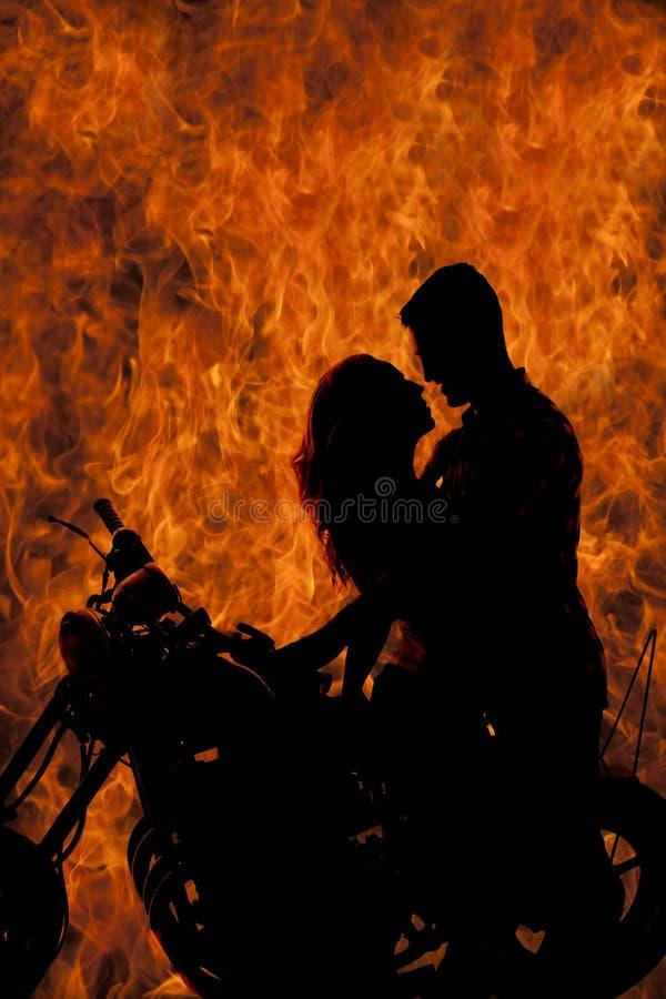 Baiser de couples de silhouette sur le feu de moto image stock
