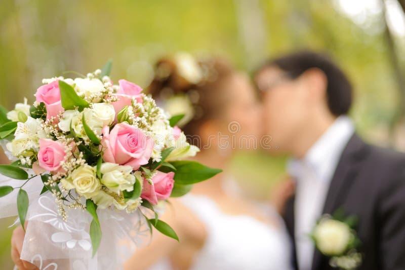 Baiser de jeunes mariés en parc image stock