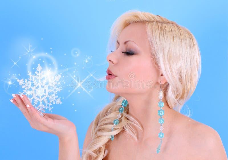 Baiser de soufflement de jeune femme avec des flocons de neige et des étoiles sur le bleu photographie stock libre de droits