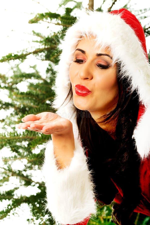 Baiser de soufflement de femme de Santa image libre de droits