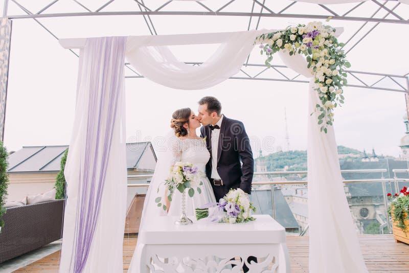 Baisers des couples de nouveaux mariés sous la voûte de mariage image libre de droits