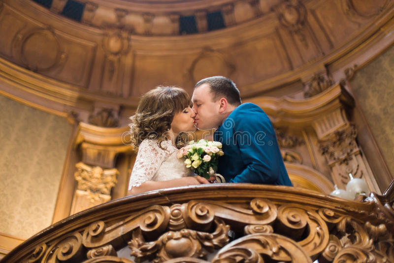 Baisers des nouveaux mariés tout en se tenant sur le vieux balcon baroque avec le bouquet de mariage photographie stock libre de droits