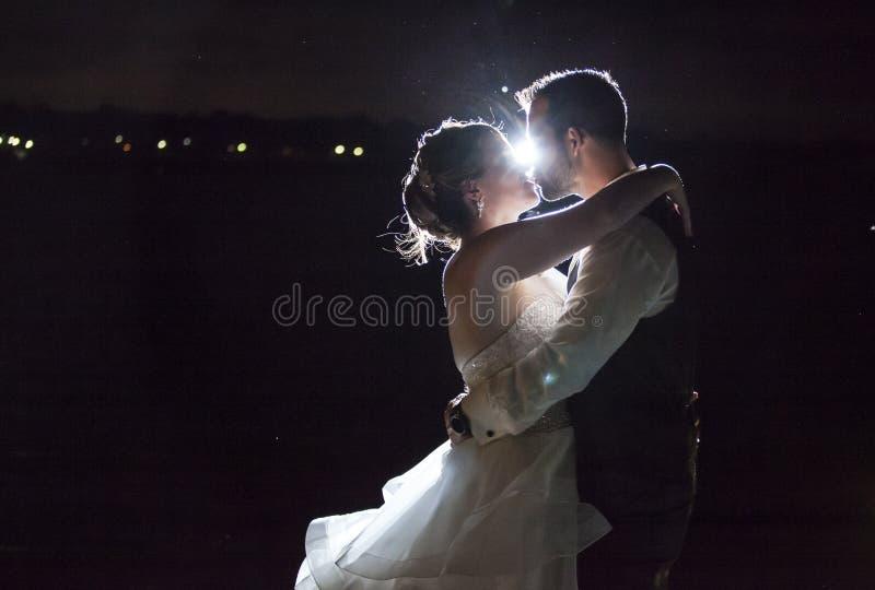Baisers rétro-éclairés de couples de mariage de nuit images libres de droits