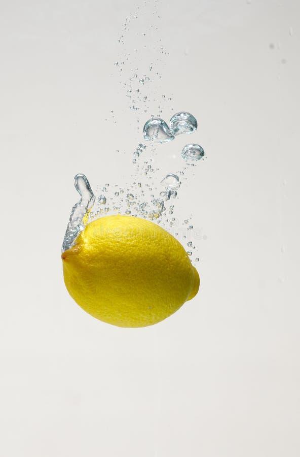 Baisse de citron fra?che sur l'eau avec la rumeur images stock