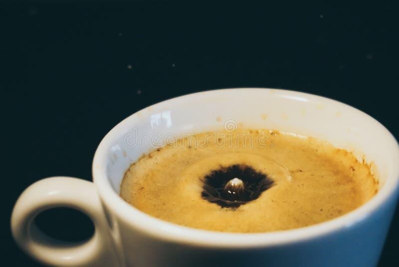 Baisse de lait tombant dans une tasse de café image stock
