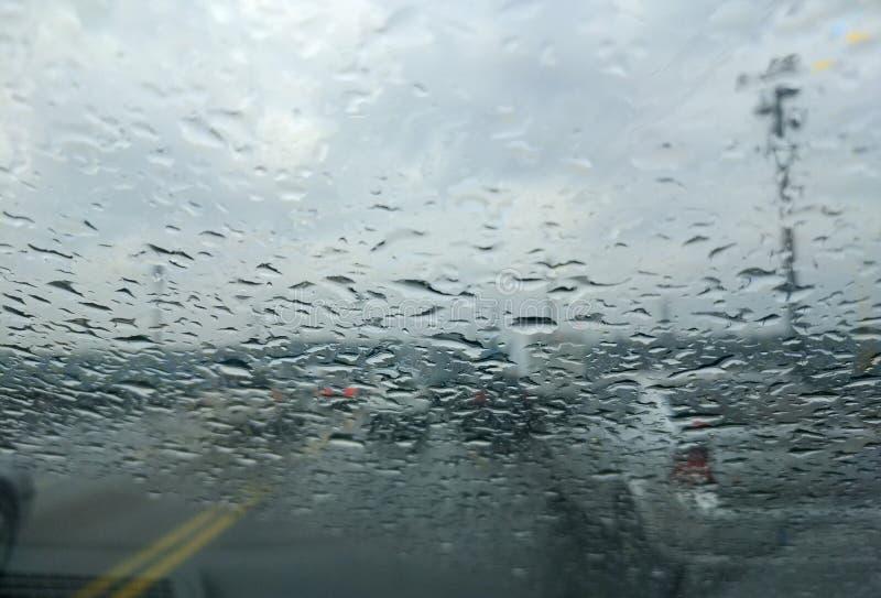 Baisse de pluie sur le fond en verre de voiture La vue de route par la fen?tre de voiture avec la pluie chute, conduisant sous la photos stock