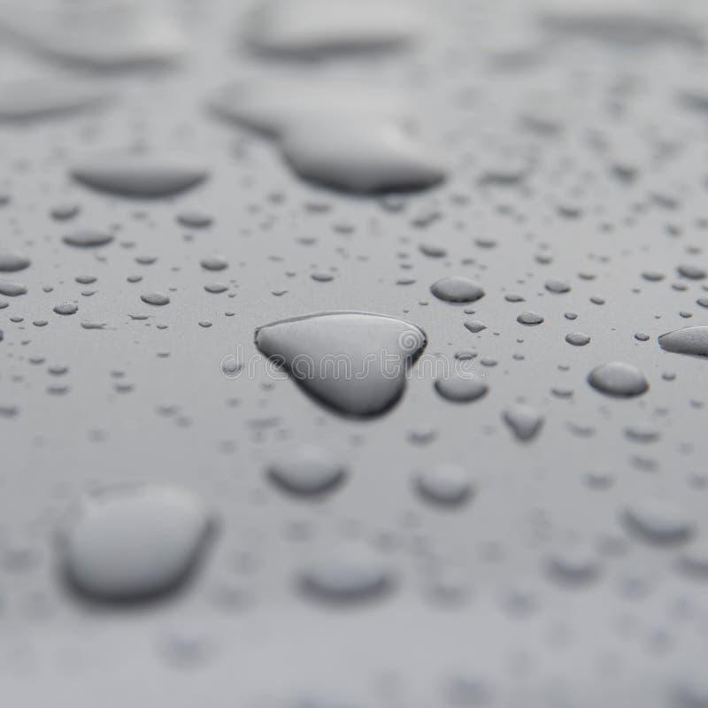 Baisse en forme de coeur inspirée de l'eau de pluie sur la surface grise images stock