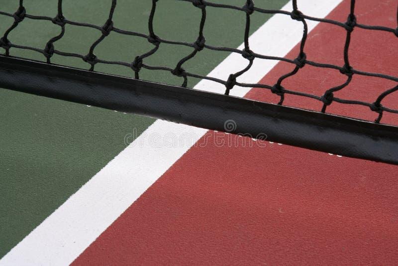 Baisses de l'eau sur le réseau de tennis photographie stock