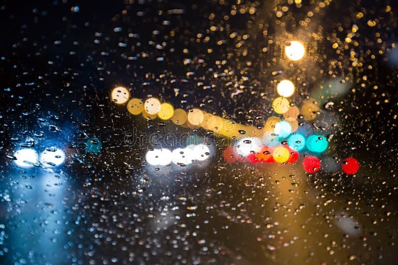 Baisses de pluie sur le pare-brise la nuit photo stock