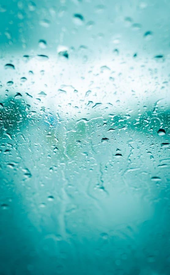 Baisses de pluie sur le verre vert de voiture avant images libres de droits