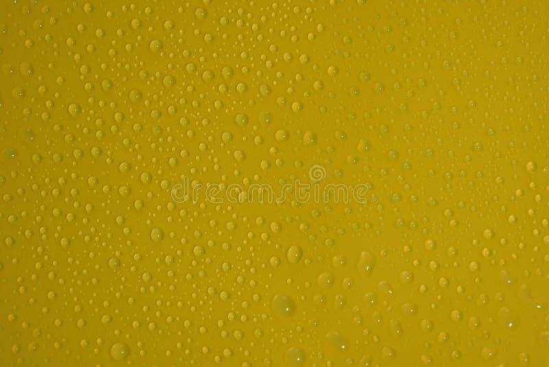 baisses naturelles de l'eau sur la texture jaune de fond photos stock